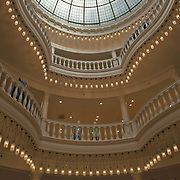 """De luxe warenhuizen van Maison de Bonneterie in Amsterdam en Den Haag gaan na 125 jaar hun deuren sluiten. Door de aanhoudende recessie is het economisch niet langer verantwoord om de winkels open te houden.<br /> Het eerste filiaal van Maison de Bonneterie werd in 1889 geopend aan de Kalverstraat in Amsterdam. Het tweede filiaal werd in 1913 geopend op de hoek van de Gravenstraat en het Buitenhof in Den Haag.<br /> Het bedrijf vraagt geen faillissement aan, dat wil de Maison de Bonneterie hiermee juist voorkomen, aldus de woordvoerder. Volgens het bedrijf is er """"niet voldoende zicht meer op economisch herstel"""" en is het door """"de te lang aanhoudende en buitengewoon hardnekkige recessie in de detailhandel economisch niet langer verantwoord de activiteiten voort te zetten"""". Foto: interieur van De Bonneterie, de eerste en tweede verdieping en lichtkoepel."""