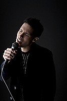 Young man singing into microphone