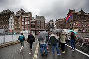 Toeristen staan in de regen te luisteren naar hun gids bij het Rokin in Amsterdam.<br /> <br /> Tourists listen to the guide at the Rokin in Amsterdam in the pouring rain.