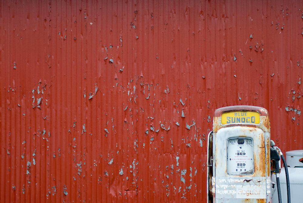 Blue Sunoco gas pump against red wall