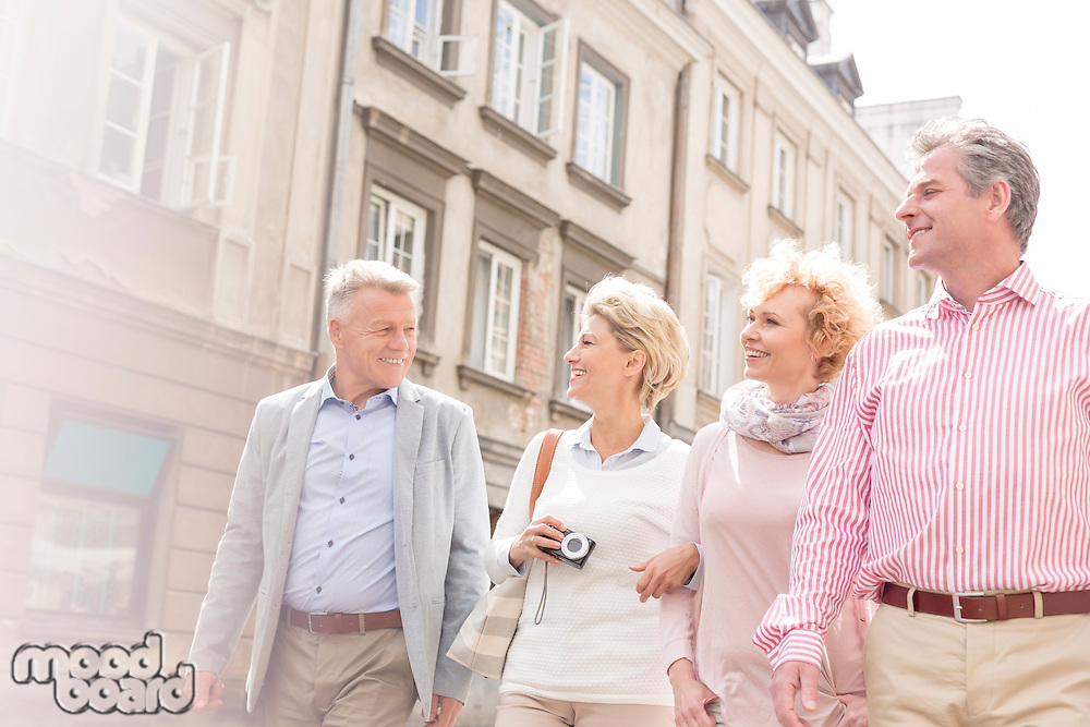 Happy friends talking while walking in city