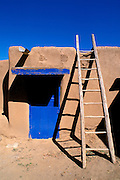 Ladder and adobe house with blue door, South House, Taos Pueblo, New Mexico