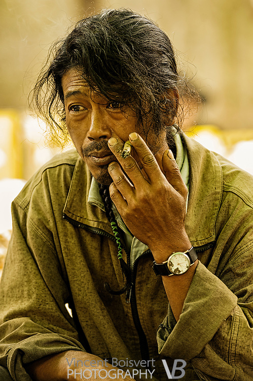 a man thinking while smoking a cigar in a street market in kalaw, myanmar