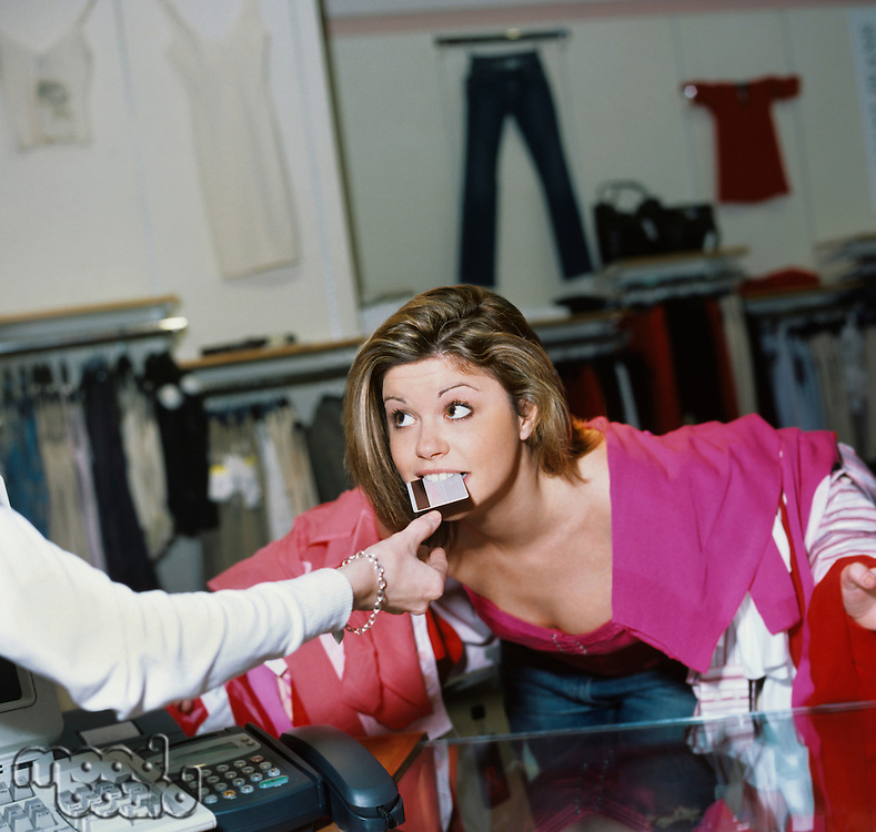 Woman laden with clothes handing credit card to salesclerk with mouth
