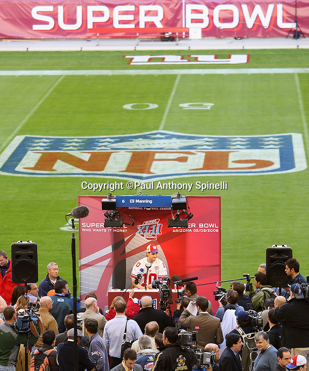 GLENDALE, AZ - JANUARY 29: The NFL Shield, NY Giants logo, and Super Bowl banner on the side of the playing field serve as backdrops as quarterback Eli Manning #10 of the New York Giants speaks to the media at the Giants Super Bowl XLII Media Day at University of Phoenix Stadium on January 29, 2008 in Glendale, Arizona.©Paul Anthony Spinelli *** Local Caption *** Eli Manning