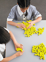 Elementary students playing with dice on desk elevated view