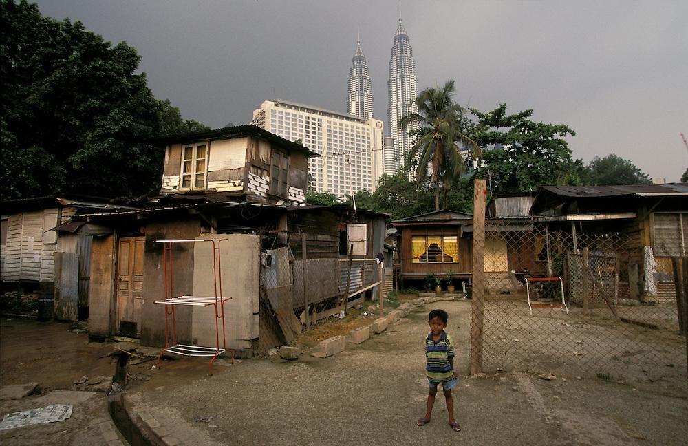 Malaysia, Kuala Lumpur..Architecture. Poverty. Contrast. The Petronas Twin Towers, a luxury hotel (Radisson) and slum housing...©Mark Henley