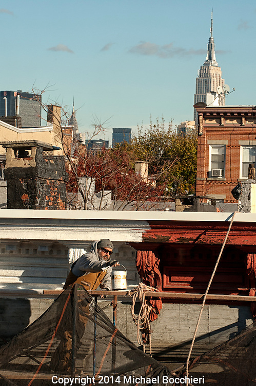 HOBOKEN, NJ - November 14:  A man works repairing a building on a scaffold on November 14, 2014 in HOBOKEN, NJ.  (Photo by Michael Bocchieri/Bocchieri Archive)