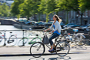 Young woman wearing high heels shoes cycling out for the evening across bridge in Amsterdam, Holland