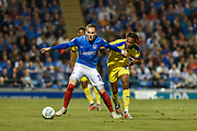 Portsmouth Midfielder, Ronan Curtis (11) holds off AFC Wimbledon Defender, Toby Sibbick (20) during the Carabao Cup match between Portsmouth and AFC Wimbledon at Fratton Park, Portsmouth, England on 14 August 2018.
