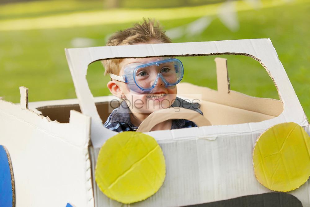 Boy Wearing Goggles Driving Cardboard Car