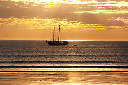 The sun's last rays catch a lugger sailing home on Broome's Cable Beach.