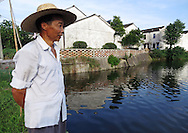 Mr Wang looking out over his fish pond, Shezhong Village, Linghu County, Zhejiang Province, China.  Mr Wong's family farms fish and silkworms in an integrated nd  sustainable system of fish farming and silk production.