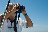 Man looking through binoculars on boat