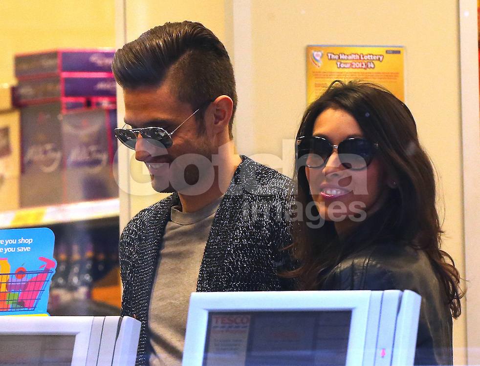 Arsenal striker Olivier Giroud and his stunning wife Jennifer out shopping together in north London. The pair walked hand in hand, looking very much in love dispite Olivier's alleged hotel tryst with glamour FHM model Celia Kay in February. After browsing the shops and picking up supplies from a local Tesco's, the pairs public display of affection continued as they stopped for a loving kiss, before heading back to their car. UK. 12/03/2014 <br />