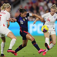 United States forward Carli Lloyd (10) shoots between England defender Steph Houghton (5) and England defender Leah Williamson (14) during the first match of the 2020 She Believes Cup soccer tournament at Exploria Stadium on 5 March 2020 in Orlando, Florida USA.