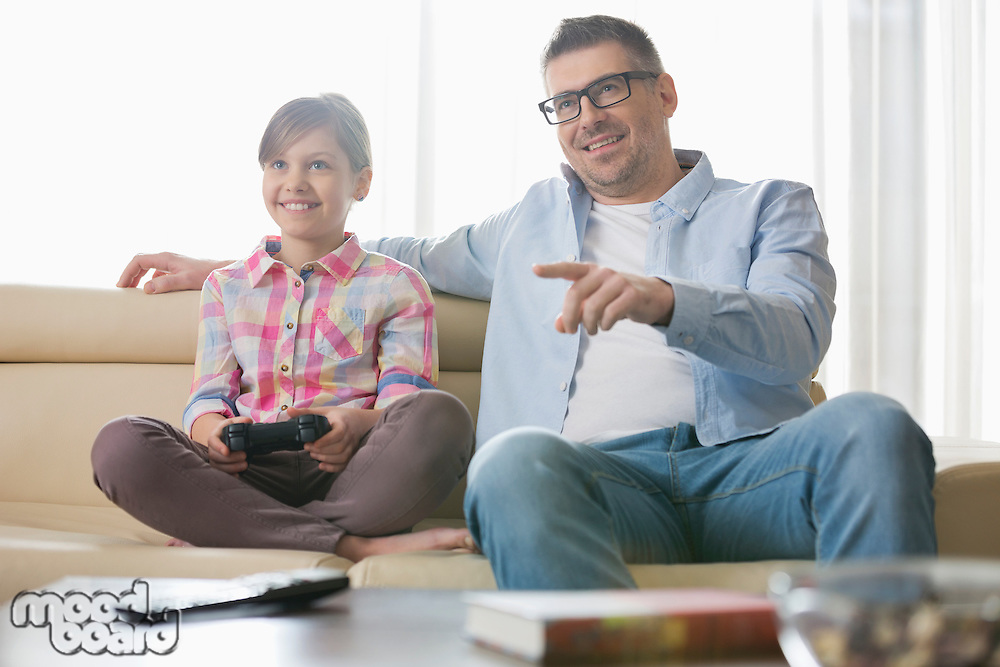Happy father and daughter playing video game in living room