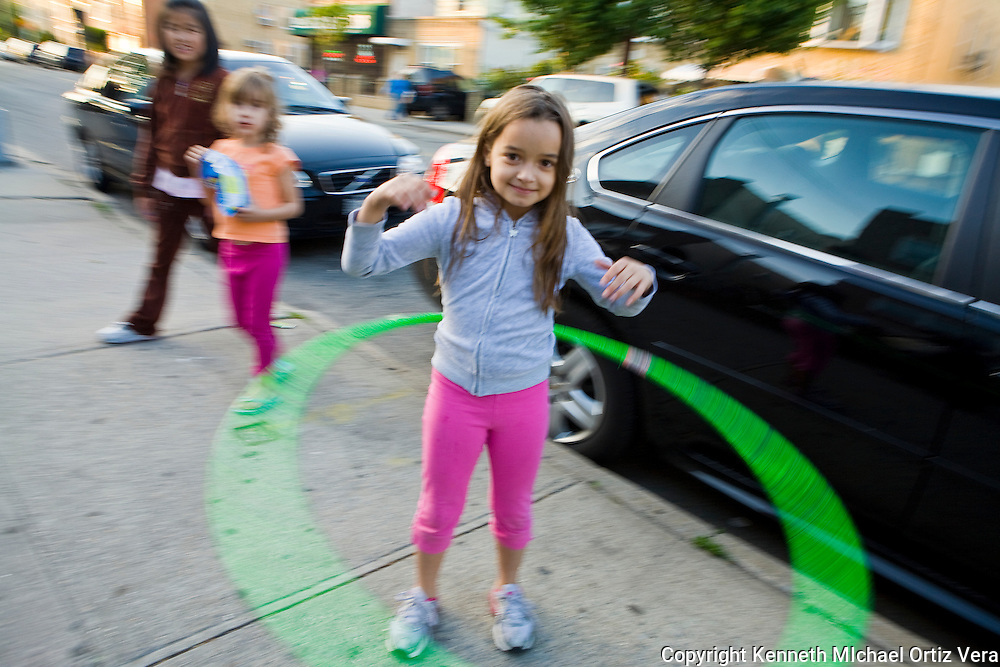 A happy little girl in Astoria Queens is having fun with her green Hulahoop in front of her home, while another girl walks by eating her potato chips.