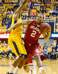 Feb 20, 2016; Morgantown, WV, USA; Oklahoma Sooners guard Dinjiyl Walker (2) drives down the lane guarded by West Virginia Mountaineers guard Tarik Phillip (12) during the first half at the WVU Coliseum. Mandatory Credit: Ben Queen-USA TODAY Sports