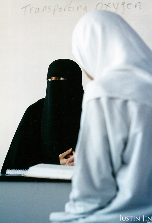 A veiled teacher from Malawi teaches the koran to British-born Muslims at a madrassa (Koran school) in Leicester city. Muslims rent the premise, normally a public state school, during the evenings to educated their young. ....The words 'transporting oxygen' were left over during a chemistry class. ....Leicester is expected to be the first city in the UK to have a majority non-white population within the next few years. It is one of the most ethnically-diverse cities in Europe. ......Picture taken April 2005 by Justin Jin