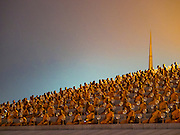 """22 FEBRUARY 2016 - KHLONG LUANG, PATHUM THANI, THAILAND:  Monks sit around the chedi during the Makha Bucha Day service at Wat Phra Dhammakaya.  Makha Bucha Day is a public holiday in Cambodia, Laos, Myanmar and Thailand. Many people go to the temple to perform merit-making activities on Makha Bucha Day, which marks four important events in Buddhism: 1,250 disciples came to see the Buddha without being summoned, all of them were Arhantas, Enlightened Ones, and all were ordained by the Buddha himself. The Buddha gave those Arhantas the principles of Buddhism, called """"The ovadhapatimokha"""". Those principles are:  1) To cease from all evil, 2) To do what is good, 3) To cleanse one's mind. The Buddha delivered an important sermon on that day which laid down the principles of the Buddhist teachings. In Thailand, this teaching has been dubbed the """"Heart of Buddhism."""" Wat Phra Dhammakaya is the center of the Dhammakaya Movement, a Buddhist sect founded in the 1970s and led by Phra Dhammachayo.     PHOTO BY JACK KURTZ"""