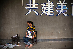 "Yang Zong Chun, 30, holding a picture of her daughter Shi Xue, 10, is seen  at Fuxin No.2 Primary  School in Wufu, Sichuan province May 24, 2008.   ""I just want people to know about what happened here."