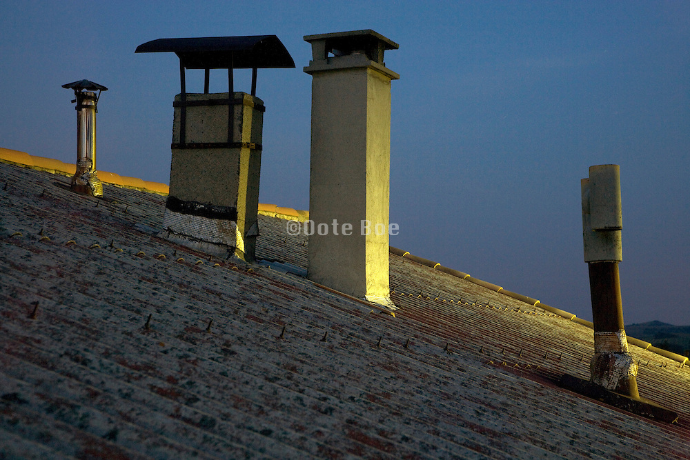 various air ducks and chimneys on top of a residential roof
