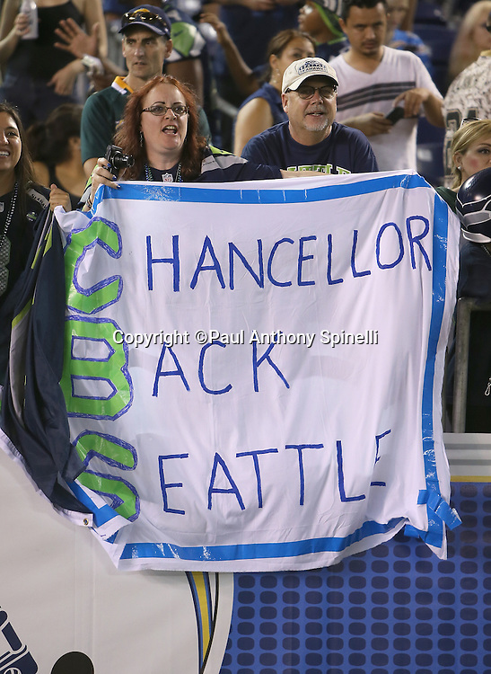 "A pair of Seattle Seahawks fans hold up a ""Chancellor Back Seattle"" sign, referring to Seattle Seahawks preseason holdout Kam Chancellor, during the 2015 NFL preseason football game against the San Diego Chargers on Saturday, Aug. 29, 2015 in San Diego. The Seahawks won the game 16-15. (©Paul Anthony Spinelli)"