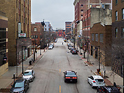 """24 MARCH 2020 - DES MOINES, IOWA: A person crosses a street in an historic neighborhood in downtown Des Moines Tuesday. Many of the city residents chose to stay in Tuesday and the downtown area was deserted. On Tuesday morning, 24 March, Iowa reported over 120 confirmed cases of the Coronavirus (SARS-CoV-2) and COVID-19. Restaurants, bars, movie theaters, places that draw crowds are closed for at least 30 days. The Governor has not ordered """"shelter in place""""  but several Mayors, including the Mayor of Des Moines, have asked residents to stay in their homes for all but the essential needs. People are being encouraged to practice """"social distancing"""" and many businesses are requiring or encouraging employees to telecommute.       PHOTO BY JACK KURTZ"""