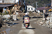 A postman on a Japan Post motorbike drives through the rubble  in Higashimatsushima, Miyagi Prefecture, Japan on  23 March 20011.  Some 350 motorcycles 160 four-wheel vehicles were destroyed by the magnitude 9 earthquake and tsunamis that swept through Japan's northeast on March 11. Photographer: Robert Gilhooly