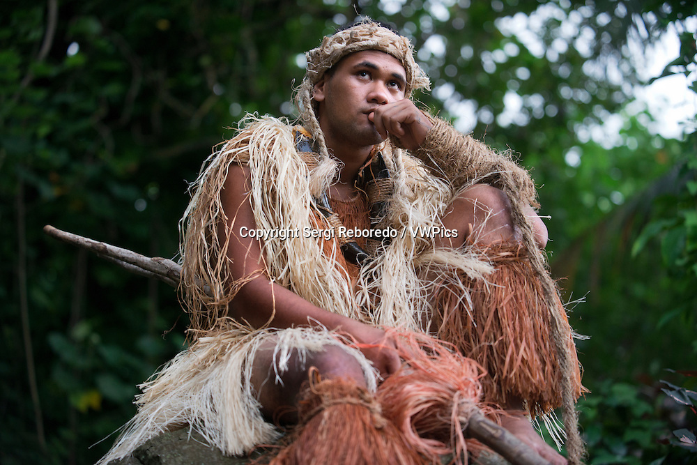 Rarotonga Island. Cook Island. Polynesia. South Pacific Ocean. A man with clothes of Maori hunter in Highland Paradise Cultural Village show.  In the mid 1980s, the late Raymond Pirangi Senior , a Rangatira (subchief) from the prominent Rarotongan Tinomana Tribe , took it upon himself to set out to reclaim his heritage from the daunting dense bush and steep hillsides of Maungaroa. His dream and determination to share all this with the rest of the world has resulted in the resurrection of one of the Cook Islands' most important historic sites. Located high up in the rugged mountains of Rarotonga, overlooking the aqua lagoon, fringing coral reef and Pacific Ocean, this unspoiled, breathtaking 205 acre site is of significant cultural heritage and was a safe spiritual and fortress haven for families, warriors and the Tinomana chiefly line for countless hundreds of years. The Highland Paradise Cultural Centre offers a truly interactive experience for locals and visitors alike. Here, you will personally relive our Polynesian yesterdays through self guided or interactive guided on-site gentle strolling tours amongst the lush gardens, village remains, replica ares (houses), historical areas of great significance and towering native trees.