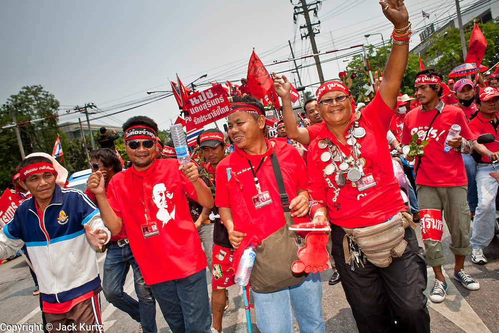 "Mar. 27, 2010 - BANGKOK, THAILAND: Red Shirts march through the streets of Bangkok Saturday, March 27. More than 80,000 members of the United Front of Democracy Against Dictatorship (UDD), also known as the ""Red Shirts"" and their supporters marched through central Bangkok March 27 during a series of protests against and demand the resignation of current Thai Prime Minister Abhisit Vejjajiva and his government. The protest is a continuation of protests the Red Shirts have been holding across Thailand. They support former Prime Minister Thaksin Shinawatra, who was deposed in a coup in 2006 and went into exile rather than go to prison after being convicted on corruption charges. Thaksin is still enormously popular in rural Thailand.    PHOTO BY JACK KURTZ"