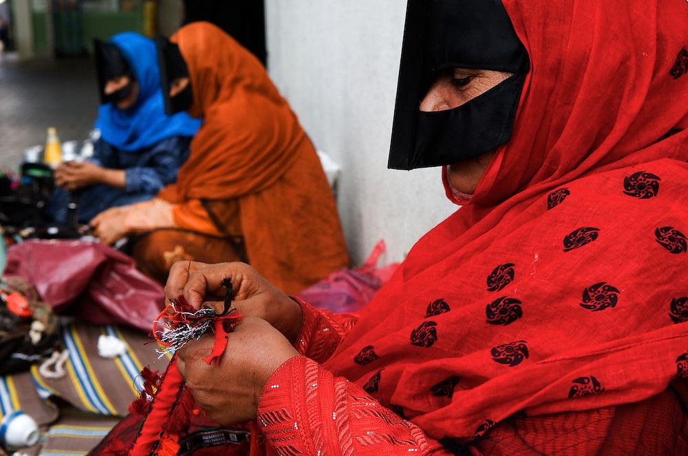 UAE: Abu Dhabi.Al Ain. Beduin women, wearing the burkha, weaving in the daily market.