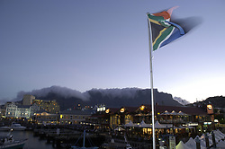South African flag flying over the shops and restaurants of the Victoria and Albert Waterfront area at dusk with Table Mountain behind, Cape Town, South Africa. (Credit Image: © Axiom/ZUMApress.com)