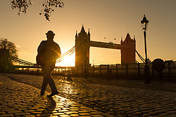 © Licensed to London News Pictures. 26/11/2017. London, UK. A man walks along the Thames path next to Tower Bridge on the River Thames at sunrise this morning during cold and clear weather. Photo credit: Vickie Flores/LNP