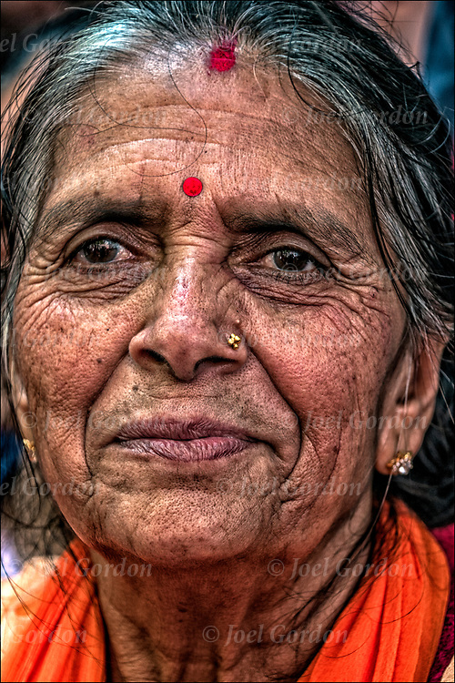 Nepalese ethnic pride head and shoulders portrait of elderly smiling Nepalese woman dressed in regalia and traditional Nepal clothing at the &ldquo;Nepal Day Parade.&rdquo; <br /> <br /> The dot between her eyes meaning she is married and the dot below her hair line is the third eye.<br /> <br /> Nepal is a landlocked country in South Asia and occupies an area of 56,136 square miles. Located between China and India, Nepal is known for its majestic Himalayas and is the home of Mount Everest, the highest peak in the world. Nepal is also the birthplace of Lord Buddha. The national capital is Kathmandu.