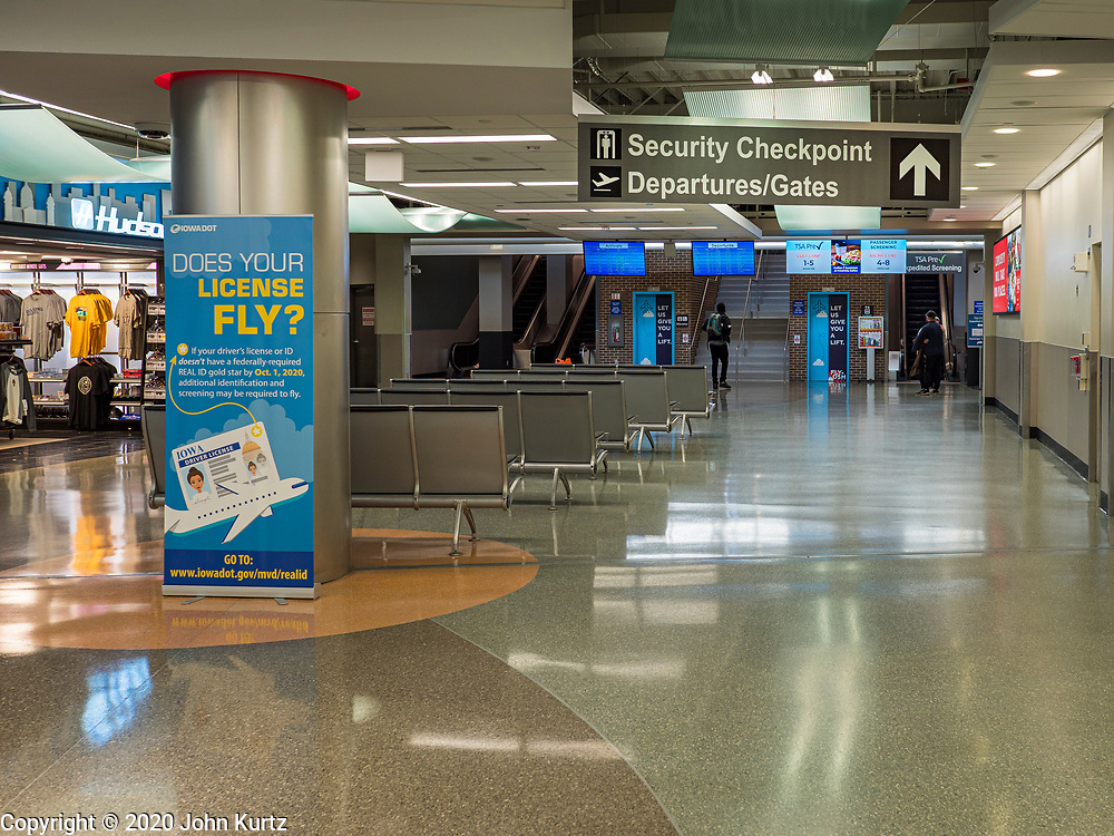 """17 MARCH 2020 - DES MOINES, IOWA:  The empty main hall at Des Moines International Airport Tuesday morning. Sunday night, the Governor announced that the state health department had recorded """"community spread"""" in Des Moines. Tuesday, the Governor ordered all restaurants and bars to close or go to take out only. The Iowa Department of Public Health has urged all public buildings, like libraries and schools, to close, and all schools in Iowa are closed for at least 30 days.     PHOTO BY JACK KURTZ"""