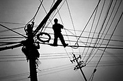 A Chinese workser upgrades electrical cables in central Beijing.