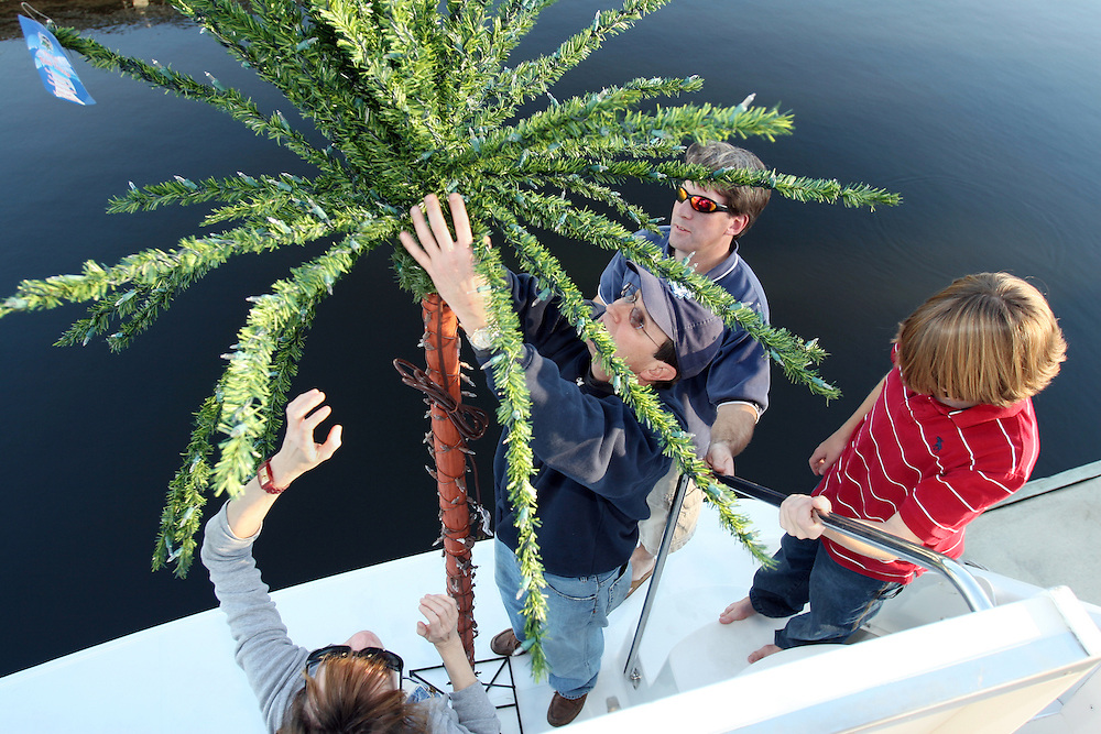 (l-r) Paula DAvis, Ken White, Tucker Stevens, and Drew Stevens prepare and decorate before the North Carolina Holiday Flotilla at Wrightsville Beach...Photo by Logan Mock-Bunting
