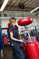Portrait of a happy female mechanic working on welding equipment in garage