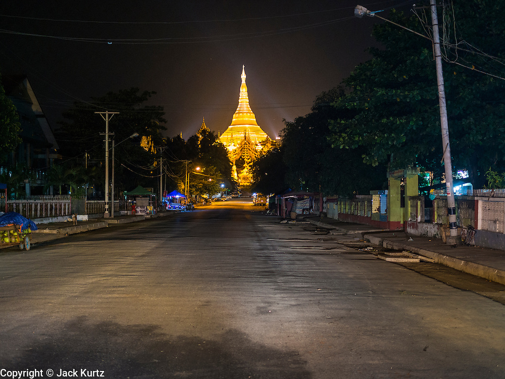 07 JUNE 2014 - YANGON, YANGON REGION, MYANMAR: Shwedagon Pagoda lit up at night in Yangon (Rangoon), Myanmar (Burma). Shwedagon Pagoda is officially called Shwedagon Zedi Daw and is also known as the Great Dagon Pagoda and the Golden Pagoda. It's a 99 metres (325 ft) gilded pagoda and stupa located in Yangon. It is the most sacred Buddhist pagoda in Myanmar with relics of the past four Buddhas enshrined within: the staff of Kakusandha, the water filter of Koṇāgamana, a piece of the robe of Kassapa and eight strands of hair from Gautama, the historical Buddha.   PHOTO BY JACK KURTZ