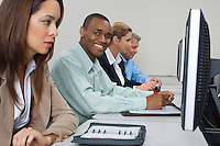Group of business people using computers in classroom, side view
