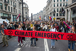 London, UK. 16th April 2019. Climate change activists from Extinction Rebellion march up Regent Street towards Oxford Circus on the second day of International Rebellion activities to call on the British government to take urgent action to combat climate change.