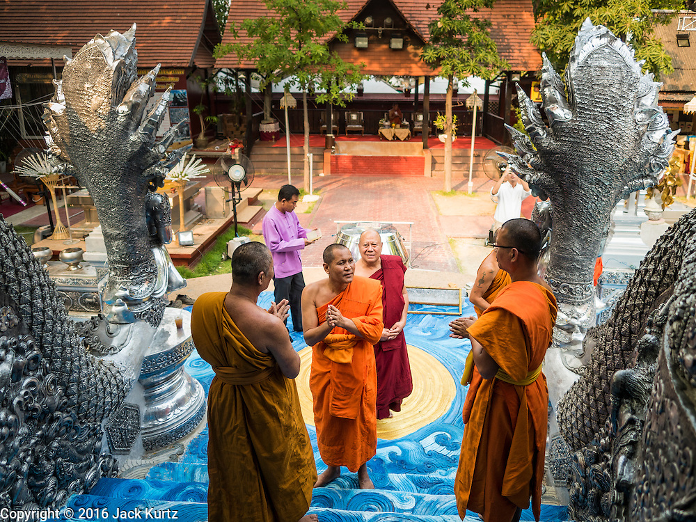 """03 APRIL 2016 - CHIANG MAI, THAILAND:  Buddhist monks walk into the ordination hall of Wat Sri Suphan. Wat Sri Suphan is also known as the """"Silver Temple"""" because of its silver ubosot, or ordination hall. The temple is more than 500 years old but the silver ordination hall was recently remodeled. The ordination hall is covered in silver and the interior is completely done in silver and gold. It's traditionally served as the main temple for the silversmiths of Chiang Mai, whose community is around the temple.     PHOTO BY JACK KURTZ"""