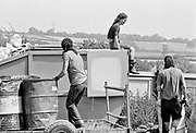 Three individuals climb rubbish bins and a skip. Glastonbury 1992