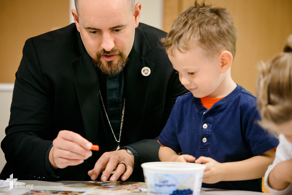 The Rev. Dr. Heath Trampe colors with a young child following worship on Sunday, Sept. 24, 2017, at Faith Lutheran Church, York, Neb. LCMS Communications/Erik M. Lunsford