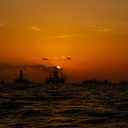 The Transocean Development Driller III and Transocean Development Driller II are silhouetted along with vessels leased by BP Plc near sunset at the BP Plc Macondo well site in the Gulf of Mexico off the coast of Louisiana, U.S., on Thursday, July 29, 2010. BP Plc continues to work on a relief well to permanently plug the source of the largest oil spill in U.S. history.  Photographer: Derick E. Hingle/Bloomberg