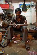 Modi street's best bicycle mechanic, Akram, pull 7:30 am to 10 pm days repairing a steady stream of utility bikes. Akram fixes an average of 25 flats per day and his father's 3-man shop rebuilds/repairs 40 wheels per day in total.  This photo was taken at the end of a particularily long day - Bombay/Mumbai - India