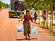 03 JUNE 2016 - SIEM REAP, CAMBODIA:  A woman carries her water home from a water distribution point in Sot Nikum, a village northeast of Siem Reap. Wells in the village have been dry for more than three months because of the drought that is gripping most of Southeast Asia. People in the community rely on water they have to buy from water sellers or water brought in by NGOs. They were waiting for water brought in by truck from Siem Reap by Water on Wheels, a NGO in Siem Reap. Cambodia is in the second year of  a record shattering drought, brought on by climate change and the El Niño weather pattern. There is no water to irrigate the farm fields and many of the wells in the area have run dry.    PHOTO BY JACK KURTZ