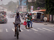 24 JANUARY 2018 - GUINOBATAN, ALBAY, PHILIPPINES:  A man rides his bike through a volcanic ash fall in Guinobatan. The Mayon volcano continued to erupt Tuesday night and Wednesday forcing the Albay provincial government to order more evacuations. By Wednesday evening (Philippine time) more than 60,000 people had been evacuated from communities around the volcano to shelters outside of the 8 kilometer danger zone. Additionally, ash falls continued to disrupt life beyond the danger zones. Several airports in the region, including the airport in Legazpi, the busiest airport in the region, are closed indefinitely because of the amount of ash the volcano has thrown into the air.   PHOTO BY JACK KURTZ